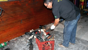 In this photo released by Policia Civil do Rio Grande do Sul, a police officer inspects victims' belongings after a fire at the Kiss nightclub in Santa Maria City, Rio Grande do Sul state, Brazil, Tuesday, Jan. 29, 2012. (AP Photo / Policia Civil do Rio Grande do Sul)