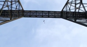 In this image taken from YouTube, daredevil Johnny Korthuis jumps from a railway bridge in Lethbridge, Alta.