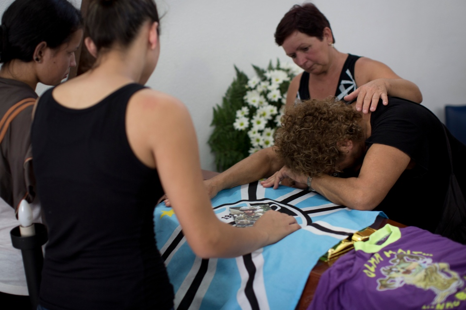 A woman mourns on the coffin containing the remains of Gustavo Gonclaves, the most recent victim of the Kiss nightclub fatal fire raising the death toll to 235, in Santa Maria, Brazil, Wednesday, Jan. 30, 2013.  (AP / Felipe Dana)