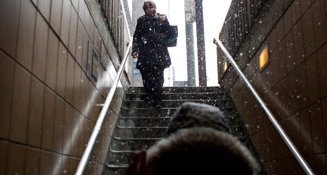 A woman walks down the steps into a subway station as snow falls in Toronto on Friday, Jan. 25, 2013. (The Canadian Press/Chris Young)