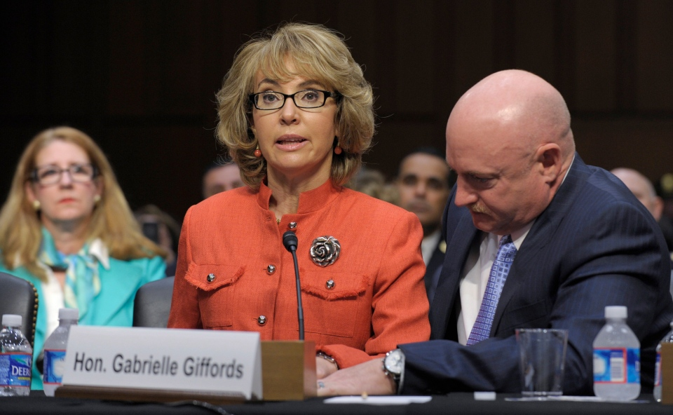 Former Arizona Rep. Gabrielle Giffords, who was seriously injured in the mass shooting that killed six people in Tucson, Ariz. two years ago, sits with her husband Mark Kelly as she speaks on Capitol Hill in Washington, Wednesday, Jan. 30, 2013. (AP / Susan Walsh)