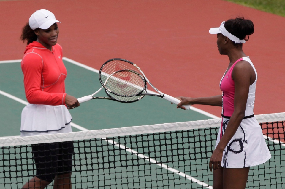 U.S. tennis players Serena Williams, left, and Venus Williams, right, greet each other before an exhibition tennis match in Lagos, Nigeria, Friday, Nov. 2, 2012. (AP / Sunday Alamba)