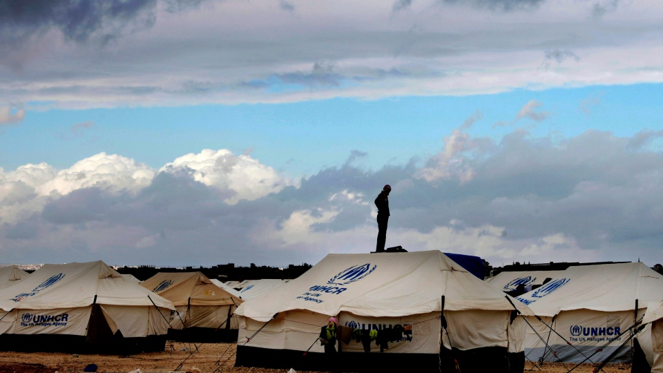 In this Wednesday, Jan. 9, 2013 file photo, a Syrian refugee stands on top of a water tank at Zaatari refugee camp, near the Syrian border in Mafraq, Jordan.  (AP Photo / Mohammad Hannon, File)