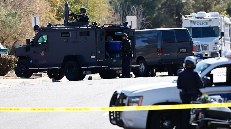 Members of the Phoenix Police Department, including the SWAT team, back left, surround the home of a suspected gunman who opened fire at a Phoenix office building, wounding three people, one of them critically, and setting off a manhunt that led police to surround his house for several hours before they discovered he wasn't there, Wednesday, Jan. 30, 2013, in Phoenix. (AP / Ross D. Franklin)