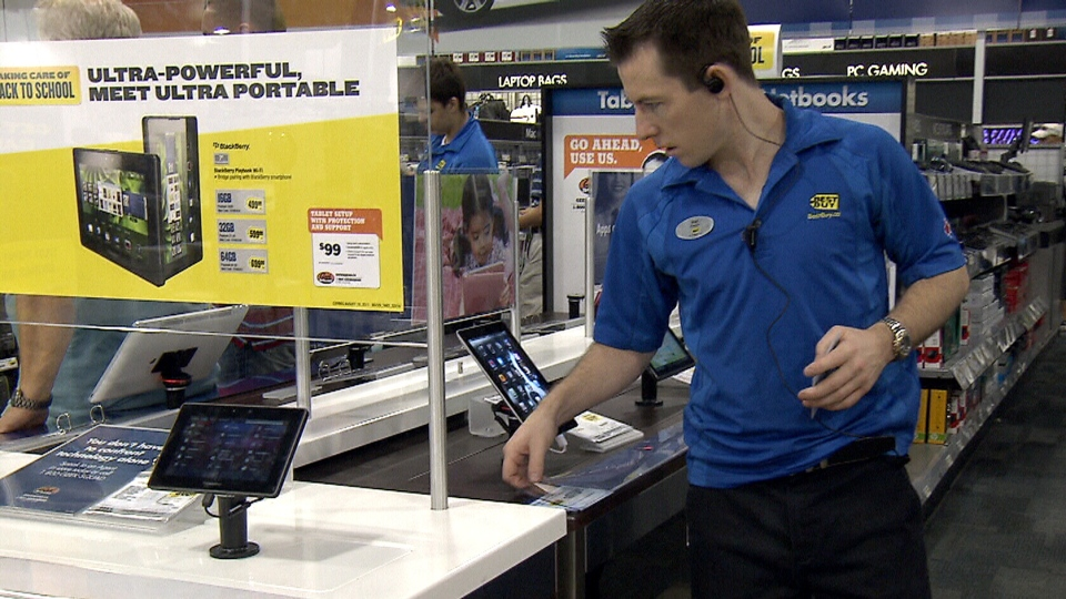 A Best Buy employee checks on a display of tablets inside a Best Buy store.