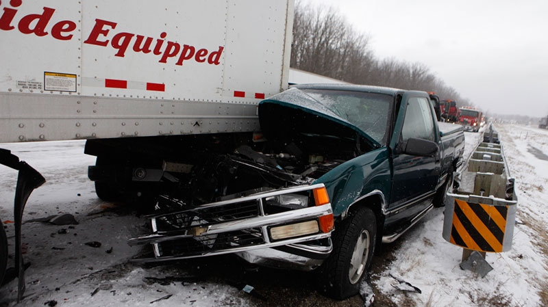 A truck is pinned under a trailer on Southbound 23 in Grand Blanc, Mich., Thursday, Jan. 31, 2013. (The Grand Rapids Press, Sammy Jo Hester)