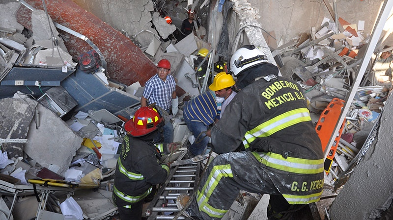 Firefighters and workers dig for survivors after an explosion at an adjacent building to the executive tower of Mexico's state-owned oil company PEMEX, in Mexico City, Thursday Jan. 31, 2013. (AP / Guillermo Gutierrez)