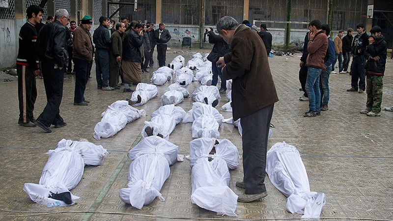 Syrian citizens search for their relatives amongst dead bodies who were found Tuesday next to a river, at the neighborhood of Bustan al-Qasr in Aleppo, Syria, Wednesday, Jan. 30, 2013. (AP / Abdullah al-Yassin)