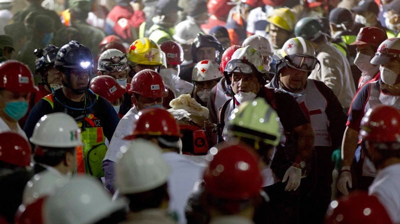 Rescue workers carry an injured survivor after an explosion in a building at Mexico's state-owned oil company PEMEX complex, in Mexico City, Thursday Jan. 31, 2013. (AP Photo/Eduardo Verdugo)