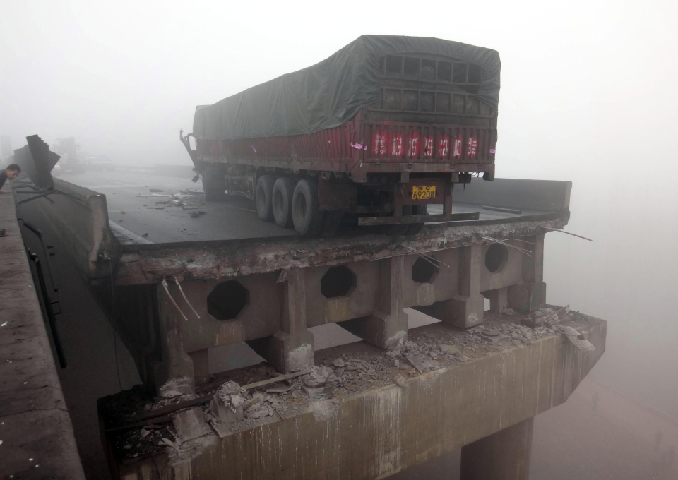 In this photo provided by China's Xinhua News Agency, a truck sits on the expressway bridge which partially collapsed due to an explosion in Mianchi County, Sanmenxia, central China's Henan Province, Thursday, Feb. 1, 2013. (AP Photo/Xinhua, Xiao Meng)