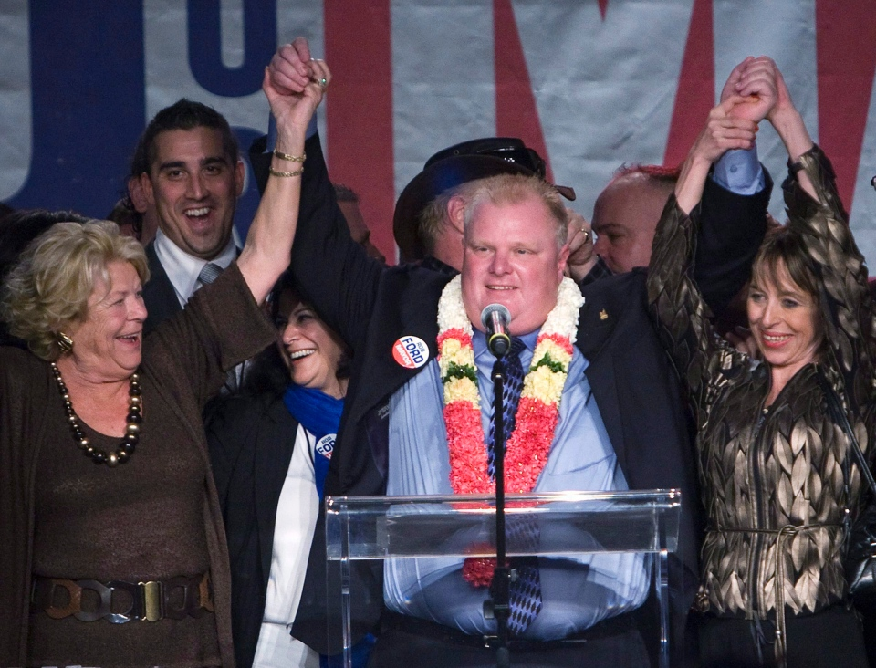 Toronto Mayor Rob Ford, centre, raises his arms with his wife Renata, right, and mother Diane, left, as he speaks to supporters in Toronto on Monday, Oct. 25, 2010. (Nathan Denette / THE CANADIAN PRESS)
