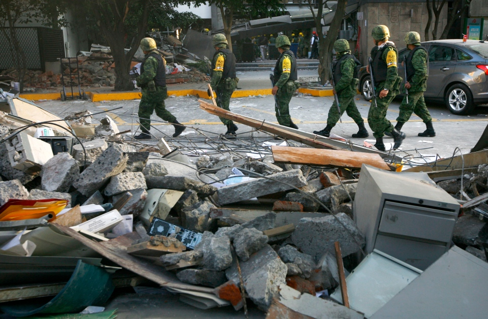 Soldiers patrol next to debris caused by an explosion at the state-owned oil company PEMEX office complex in Mexico City on Friday, Feb. 1, 2013.  (AP / Marco Ugarte)