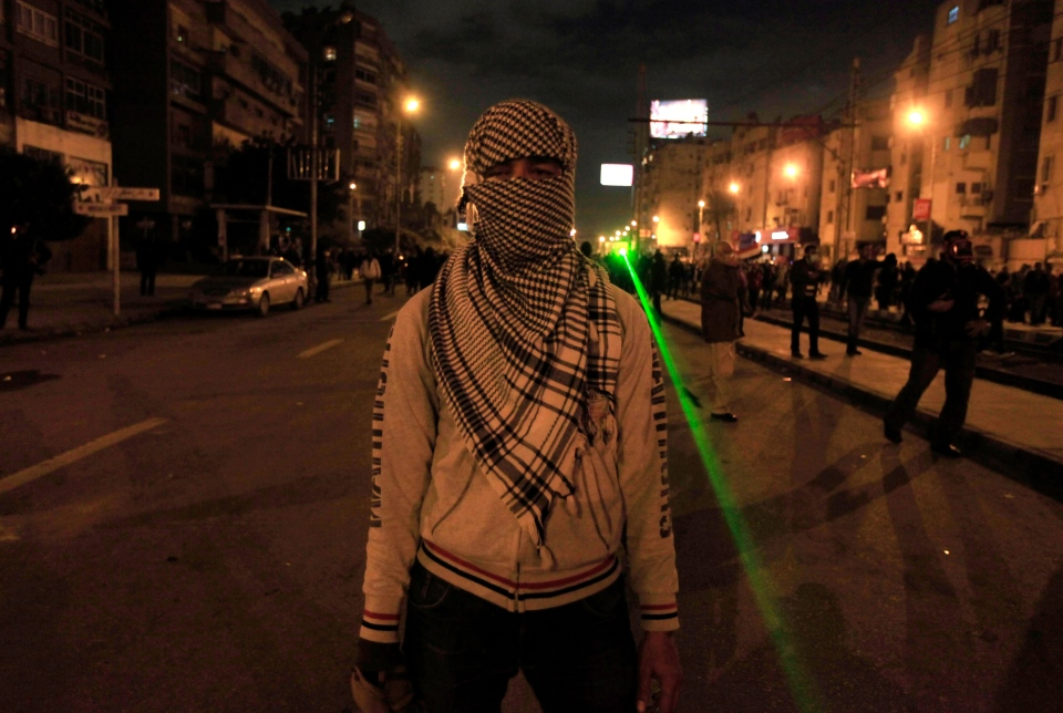 An Egyptian protester covers his face during clashes with riot police next to the presidential palace in Cairo, Egypt, Friday, Feb. 1, 2013. (AP / Khalil Hamra)
