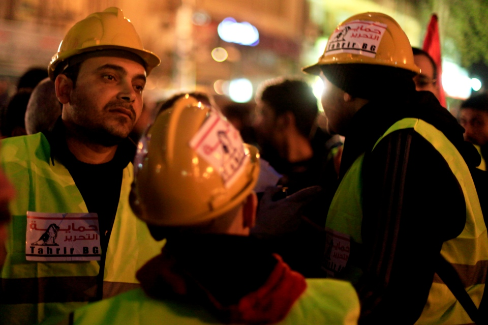 Egyptian volunteers of Tahrir Bodyguard, an anti-harassment group, work at a rally in Tahrir Square, Cairo, Egypt, Friday, Feb. 1, 2013.  (AP / Khalil Hamra)