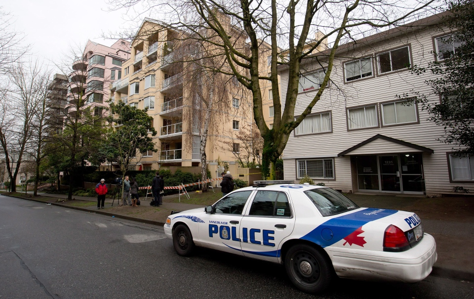 A police officer sits in a cruiser outside an apartment building in Vancouver, B.C., on Friday, Feb. 1, 2013. (Darryl Dyck / THE CANADIAN PRESS)