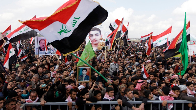 Iraqis chant anti-government slogans as they wave national flags and hold posters of slain protesters during a protest in Fallujah, 65 kilometres west of Baghdad, Iraq, Friday, Feb. 1, 2013. (AP / Khalid Mohammed)