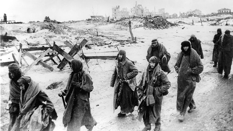 With uniforms tattered from the battle, residents make their way in the bitter cold through the ruins of Stalingrad, Russia in early 1943. (AP / hpr)