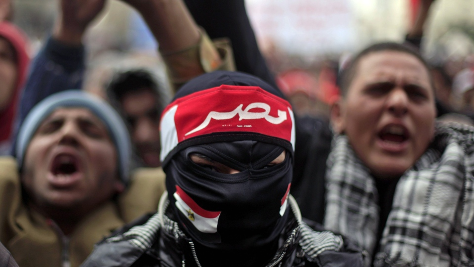 "An Egyptian masked protester wears a head banner with Arabic writing that reads ""Egypt"", during a rally in Tahrir Square, Cairo, Egypt, Friday, Feb. 1, 2013. (AP / Khalil Hamra)"