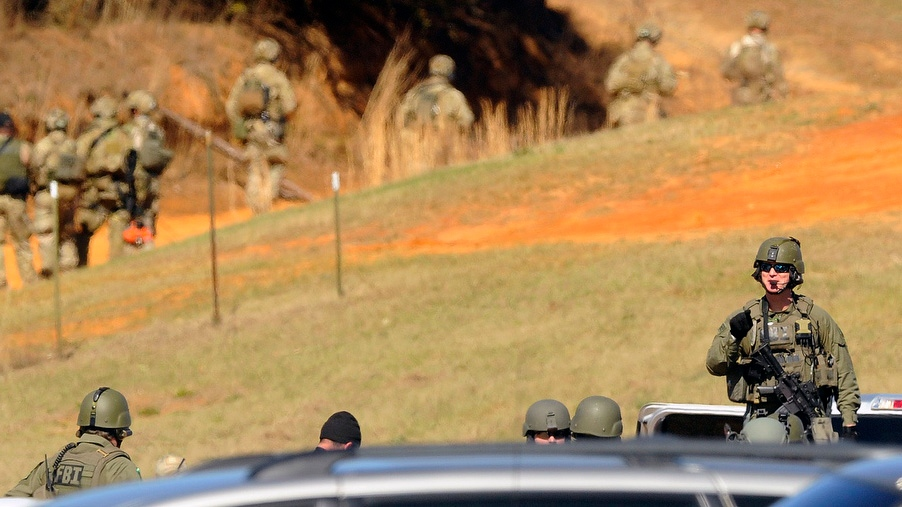 Members of the FBI team wait, Saturday, Feb. 2, 2013, in Midland City, Ala. Authorities said they still have an open line of communication with an Alabama man accused of abducting a 5-year-old child and holding him hostage in a bunker since Tuesday, Jan. 29.