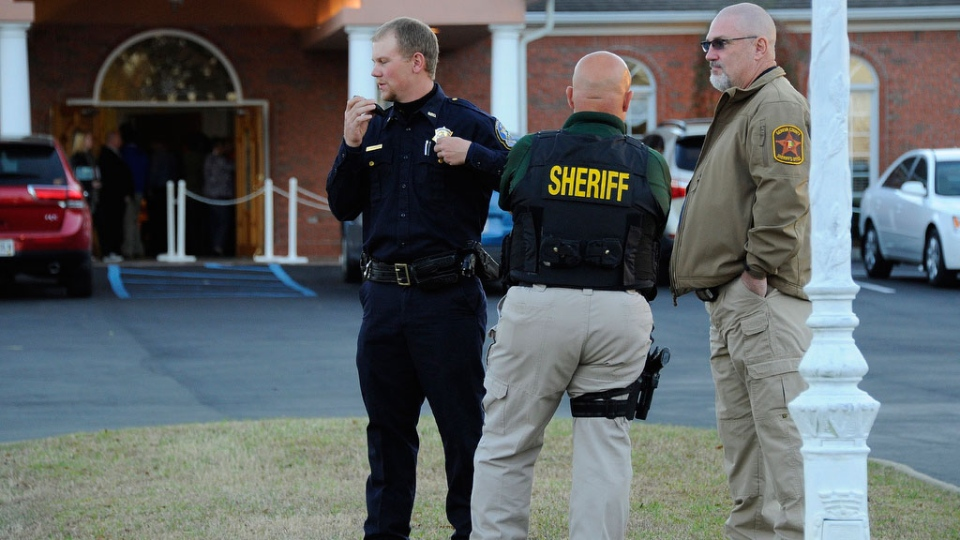 Law enforcement personnel wait outside the funeral home as people pay their respects to Charles Albert 'Chuck' Poland, the 66 year old bus driver who gave his life to save the children on his bus in Slocumb, Ala. on  Saturday, Feb. 2, 2013. (AP / AL.com, Joe Songer)
