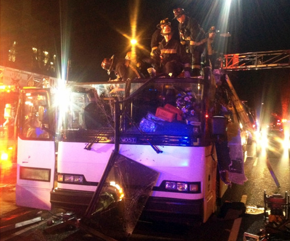 Firemen work to remove injured passengers from a bus that hit a bridge as it travelled along Soldiers Field Road in the Allston neighborhood of Boston Saturday night, Feb. 2, 2013. (Boston Fire Department via Twitter)