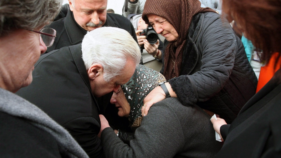 U.S. Ambassador to Turkey Francis J. Ricciardone, center left, comforts a relative of the Mustafa Akarsu, an embassy security guard killed when a suicide bomber struck the American Embassy in Turkish capital on Friday, during his funeral in Ankara, Turkey, Saturday, Feb. 2, 2013. (AP Photo)