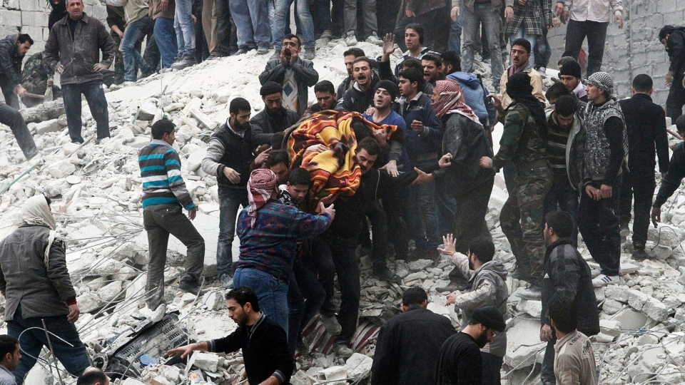 Syrian people carry a body after a government airstrike hit the neighborhood of Ansari, in Aleppo, Syria on Sunday, Feb. 3, 2013. (AP / Abdullah al-Yassin)