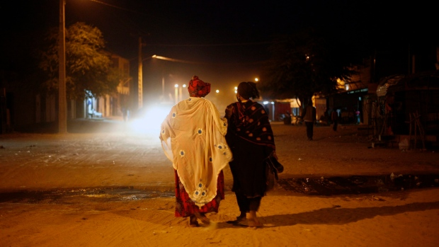 Malian women walk through streets of Timbuktu