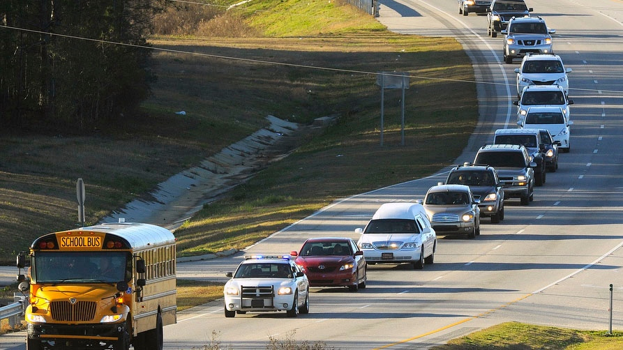 "The funeral procession of slain bus driver Charles ""Chuck"" Poland makes its way down Highway 231 in Ozark, Ala., Sunday Over 60 motorcycles and dozens of school buses join the funeral procession. (AP Photo / AL.com, Joe Songer)"