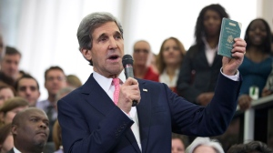 New Secretary of State John Kerry shows his first diplomatic passport he got when he was eleven years old when his father was in the foreign service, during a ceremony welcoming him as the 68th secretary of state, Monday, Feb. 4, 2013, at the State Department in Washington. (AP Photo/Manuel Balce Ceneta)