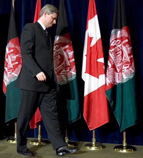 Prime Minister Stephen Harper walks past Canadian and Afghan flags in Ottawa on Monday following the press conference. (CP / Tom Hanson)