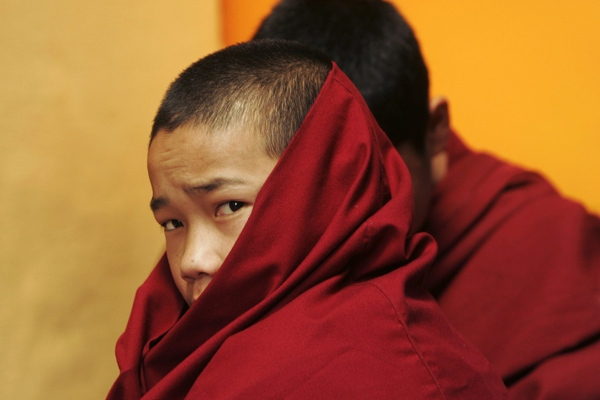 A young Tibetan Buddhist monk looks on during prayers at the Namgayal Monastery in Dharamsala, India on Thursday, March 20, 2008. (AP / Gurinder Osan)