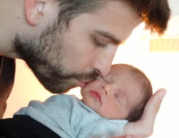 Gerard Piqué kissing his and Shakira's son Milan.