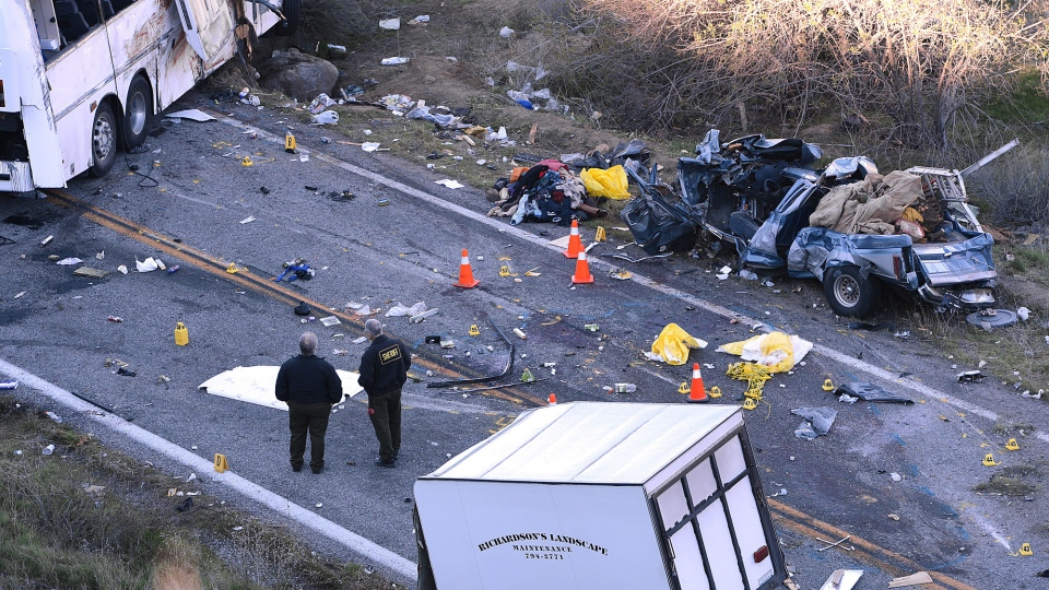 Authorities work at the scene of Sunday's fatal tour bus crash on Highway 38 north of Yucaipa, Calif., that left at least eight people dead and dozens injured on Monday Feb. 4, 2013. (AP / The Sun, Rick Sforza)