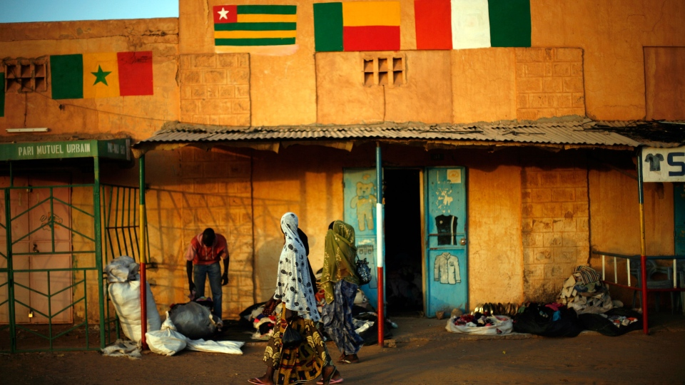 Malian women walk past a shop selling clothes in Gao, northern Mali, on the road to Gao, Monday Feb. 4, 2013. (AP / Jerome Delay)