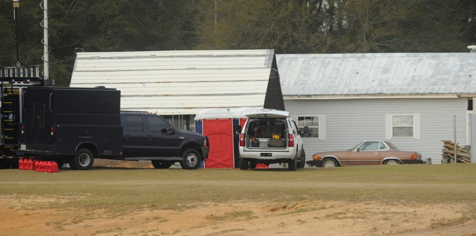 Law enforcement personnel station themselves on the property of Jimmy Lee Dykes, in Midland City, Ala., Monday, Feb. 4, 2013. (AL.com / Joe Songer)