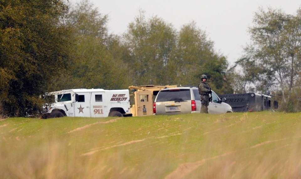 Armed law enforcement personnel station themselves near the property of Jimmy Lee Dykes, in Midland City, Ala., Monday, Feb. 4, 2013. (AL.com / Joe Songer)