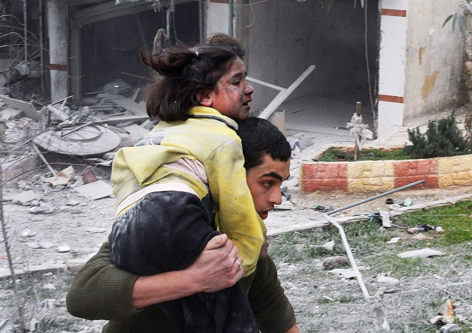 Syrian man carries his sister who was wounded in a government airstrike hit the neighborhood of Ansari, in Aleppo, Syria, Sunday, Feb. 3, 2013. (AP / Abdullah al-Yassin)