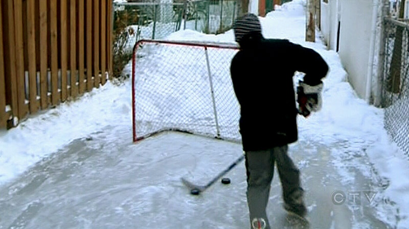 A boy plays hockey in a back alley skating rink in a neighbourhood in Montreal, Monday, Feb. 4, 2013.
