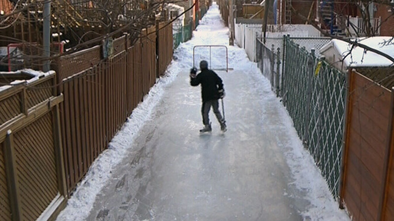 A boy plays hockey in a back alley skating rink created by residents in Montreal, Monday, Feb. 4, 2013.