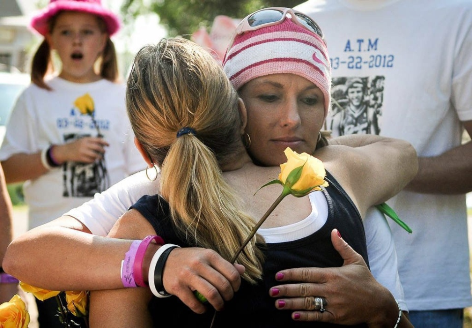 Jen Withrow, mother to 17-year-old Andrew Mulville who died by suicide in March, holds a rose as she hugs a family friend after a 5k Run/Walk to benefit programs to educate about depression and suicide in Minneapolis on Aug. 11, 2012. (AP Photo/Pioneer Press,Ben Garvin)
