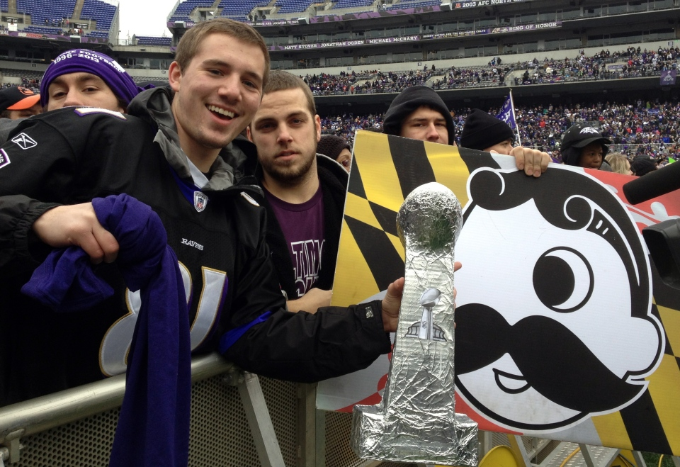 Sam Muffoletto and Phil Luzi hold up signs and a home-made Super Bowl trophy as they wait for the start of Baltimore's celebration for the Super Bowl champion parade at Ravens stadium on Feb. 5, 2013. (AP Photo/Alex Dominguez)