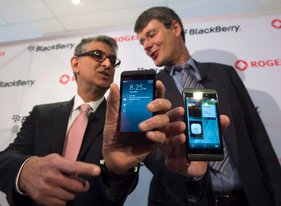 Blackberry President and CEO Thorsten Heins (right) and Rogers Communications President and CEO show off their BlackBerry Z10 devices before presenting one to the first customer at a store in Toronto on Tuesday Feb. 5, 2013. (Frank Gunn / THE CANADIAN PRESS)