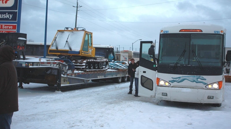 Greyhound bus passengers mull about at a gas station on Monday, Jan. 3., in White River, Ont., during a 15-hour ordeal in which they said they were abandoned by the driver.(Karina Hunter, ontarionewsnorth.com / THE CANADIAN PRES)