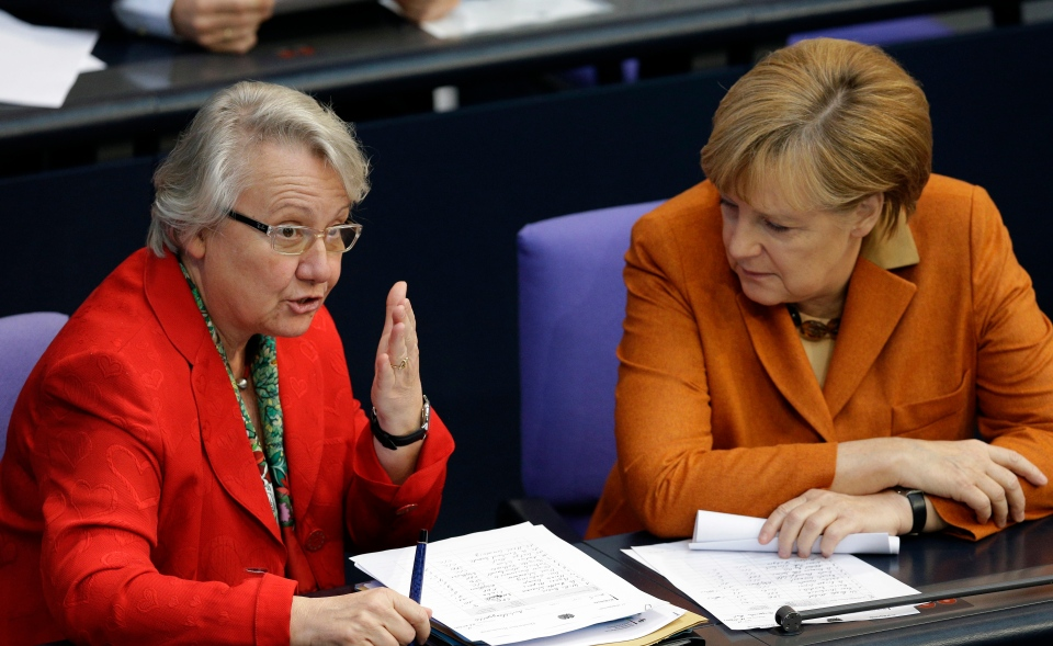 FILE - The Oct. 18, 2012 file photo shows German Science Minister Annette Schavan, left, as she talks to German Chancellor Angela Merkel, right, during a meeting of the German Federal Parliament, Bundestag, in Berlin.  (AP Photo/Michael Sohn, file)