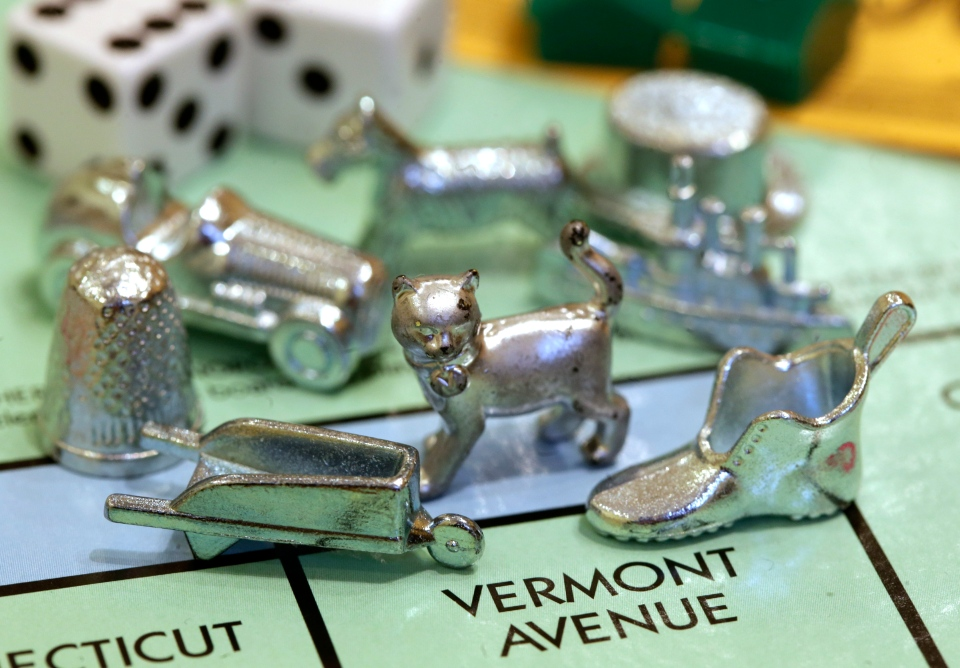 The newest Monopoly token, a cat, center, rests on a Boardwalk deed next to other tokens still in use including the wheelbarrow, left, and the shoe, right, at Hasbro Inc. headquarters, in Pawtucket, R.I., Tuesday, Feb. 5, 2013. (AP / Steven Senne)