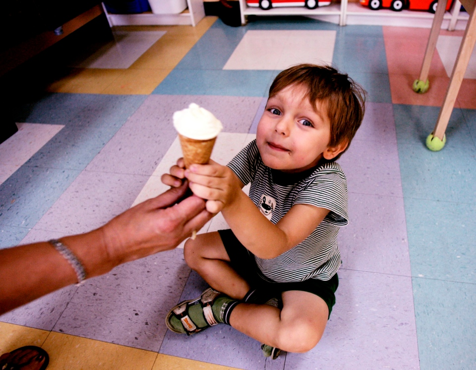 A child receives ice cream at a day care centre in Montreal on Friday, August 18, 2006. (Ian Barrett / THE CANADIAN PRESS)