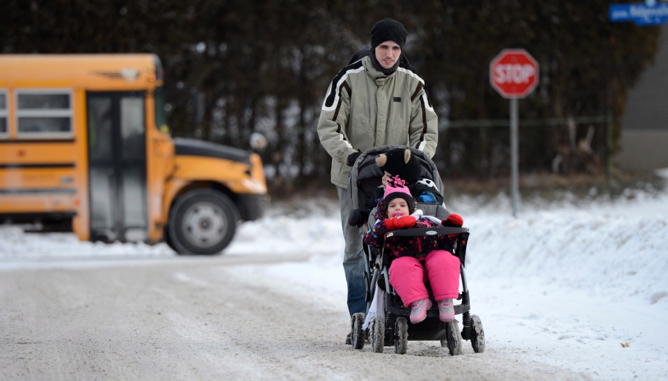 A father pushes his children in a stroller as they make their way to daycare in Ottawa on Tuesday, Jan. 22, 2013. (Sean Kilpatrick / THE CANADIAN PRESS)
