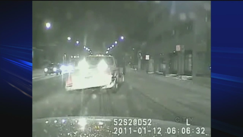 A snowplow is shown closing in on Sgt. Ryan Russell's police vehicle in this still photo taken from video from the cruiser front dashboard.