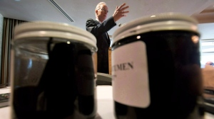 Raw bitumen and diluted bitumen are displayed in jars as newspaper publisher David Black speaks during a news conference in Vancouver, B.C., Aug. 17, 2012. (Darryl Dyck / THE CANADIAN PRESS)
